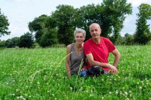 Cécile et Christion Mogis éleveurs vaches laitières bio accroupis dans l'herbe